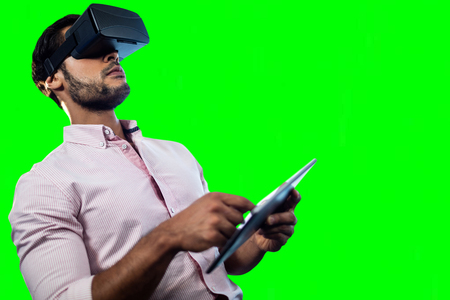 Man using an virtual glasses and a tablet against green vignette Stock Photo