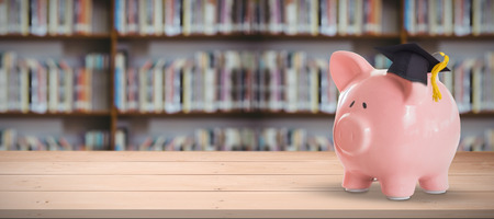 library shelf: Piggy bank with graduation hat against library shelf