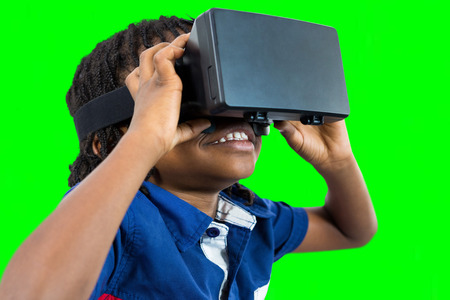virtual reality simulator: Boy wearing virtual reality simulator  against green vignette Stock Photo