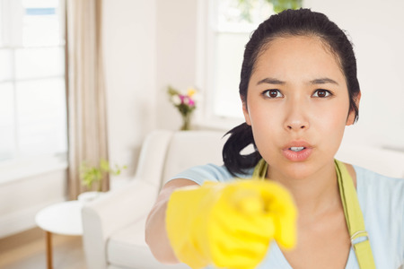 Accusing woman in apron pointing against sitting room