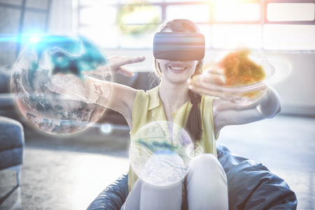 virtual reality simulator: Digital image of earth  against cheerful woman gesturing while wearing virtual reality simulator Stock Photo