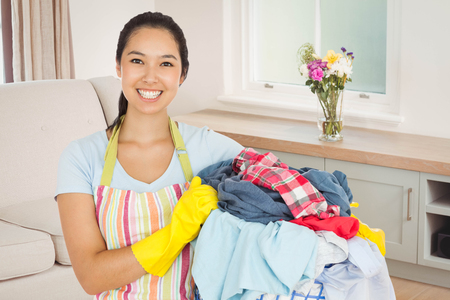 laundry basket: Laughing woman holding laundry basket against sitting room Stock Photo