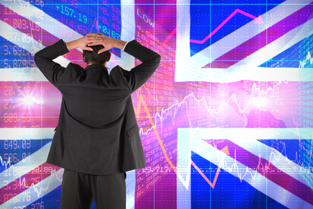 pounding head: Businessman standing back to the camera with hands on head against digitally generated uk national flag
