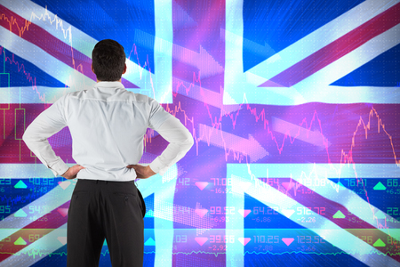 pounding head: Businessman standing back to the camera with hands on hips against digitally generated uk national flag