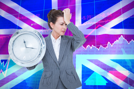 national identity: Upset businesswoman holding wall clock against digitally generated uk national flag Stock Photo
