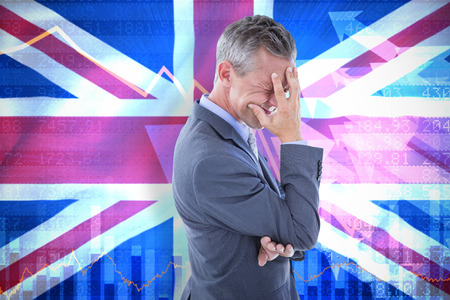 Businessman with headache against digitally generated uk national flag