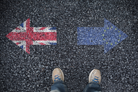 casually dressed: Casually dressed mans feet against close-up of european flag
