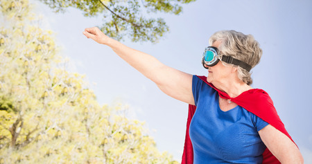 national women of color day: Senior woman wearing superwoman costume against trees in forest against sky