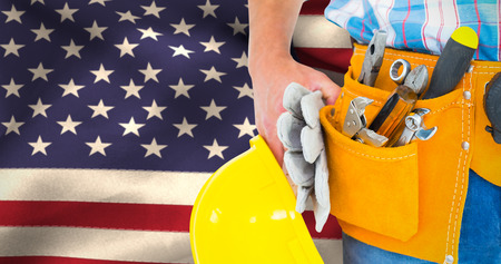red hat: Manual worker wearing tool belt while holding gloves and helmet against close-up of american flag