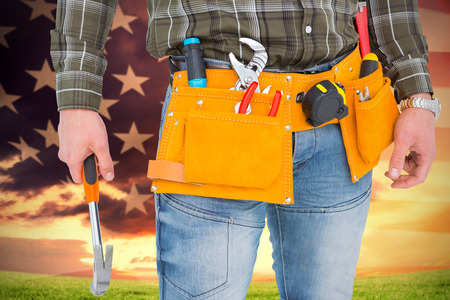american field service: Manual worker holding hammer against american flag rippling over grassy landscape Stock Photo