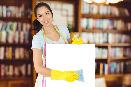 wiping: Cheerful woman wiping down white surface against view of studio