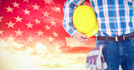 Manual worker with hard hat and gloves against composite image of united states of america flag