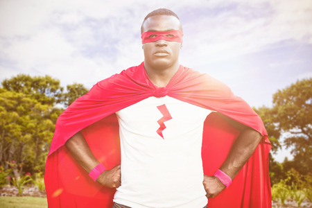national women of color day: Man wearing superhero costume against trees and plants growing at park