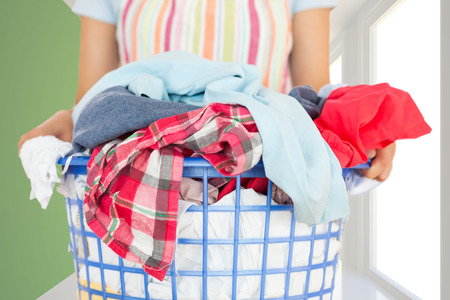 Full laundry basket against modern white and green room with window Stock Photo