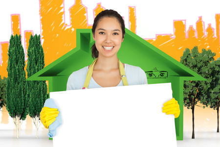 rubber gloves: Woman in apron and rubber gloves holding white surface against view of house icon