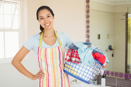 laundry basket: Happy woman with laundry basket against bathroom Stock Photo