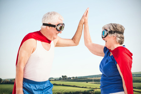 national women of color day: Senior couple wearing superman costume against scenic landscape
