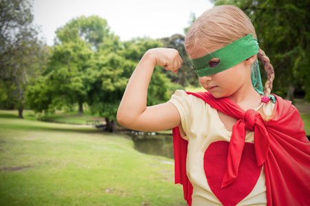 showing muscles: Girl in red cape showing muscles against lake in park