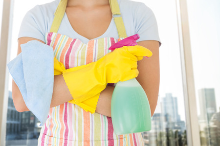 Woman holding window cleaner and rag against adhesive notes on window