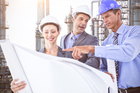 hard hats: Businessmen and a woman with hard hats and holding blueprint against view of industry