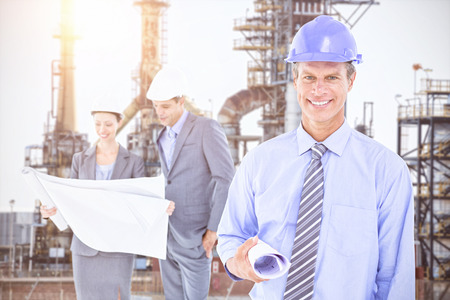 hard hats: Businessmen and a woman with hard hats and holding blueprint against image of factory Stock Photo