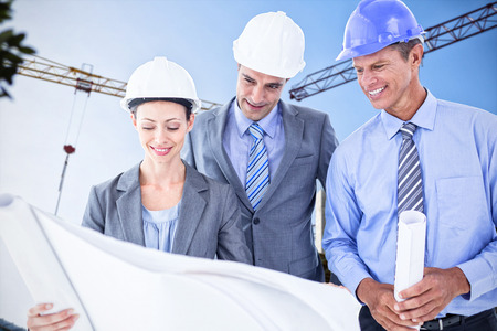 hard hats: Businessmen and a woman with hard hats and holding blueprint against crane and building construction site