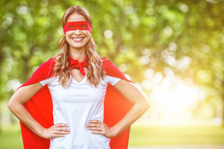 mature adult: Woman pretending to be superhero against blur view of trees