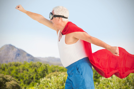 computer animation: Senior man wearing superman costume against view of landscape