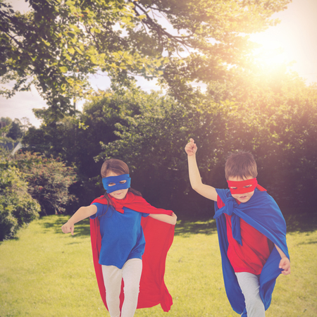 Masked kids walking pretending to be superheroes against green field