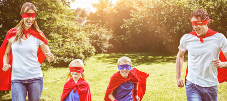 national women of color day: Happy family pretending to be superhero running against green field Stock Photo