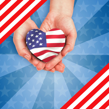 digitally generated image: Digitally generated image of hands holding heart shape American flag