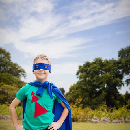 eye mask: Portrait of boy in blue eye mask and cape against trees and plants growing at park