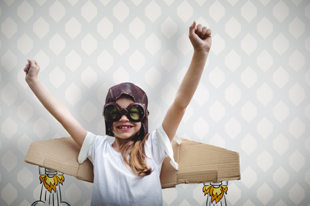 hands in: Happy girl standing with hands in the air against room with wooden floor Stock Photo