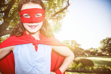 national identity: Little girl pretending to be a superhero  against view of beautiful landscape