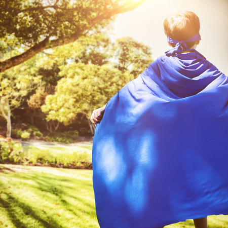 Boy in blue cape standing against bench by tree in park