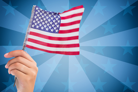 digitally generated image: Digitally generated image of human hand holding American flag against sunbrust