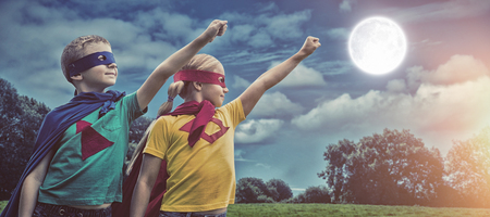 capes: Siblings in capes standing with hands raised against green field Stock Photo