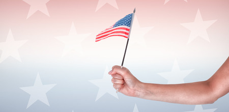 telephone pole: Cropped image of hand holding American flag against starry background Stock Photo