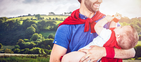 country kitchen: Country scene against father and son in superhero costume playing in kitchen