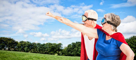 national women of color day: Senior couple wearing superman costume against green field