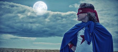 Boy wearing superhero costume  against tractor on field