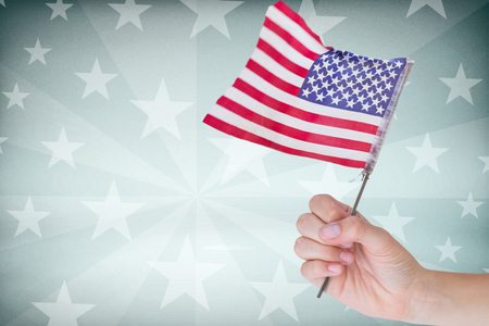 cropped: Cropped image of hand holding American flag against starry background Stock Photo