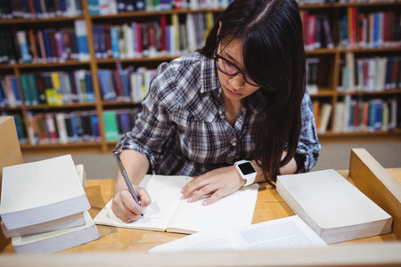 higher intelligence: Female student writing notes at desk in library