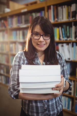 higher intelligence: Portrait of smiling female students holding a pile of books in library