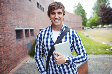 higher intelligence: Portrait of smiling student standing in college campus with digital tablet