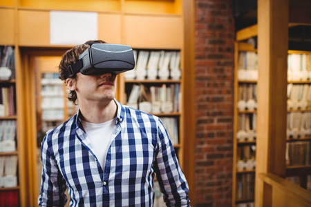 Student using virtual reality headset in library at college Stock Photo