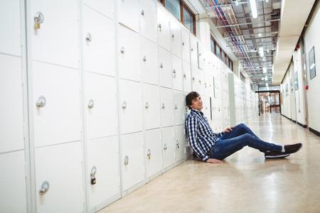 locker room: Portrait of smiling student sitting in locker room at college