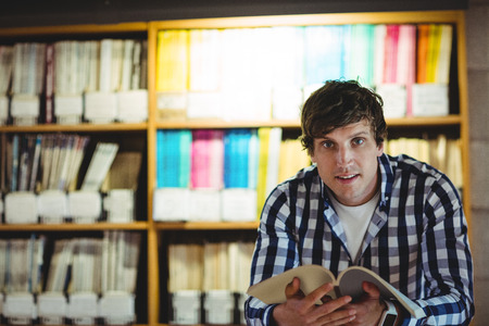 higher intelligence: Portrait of smiling student reading book in the college library Stock Photo