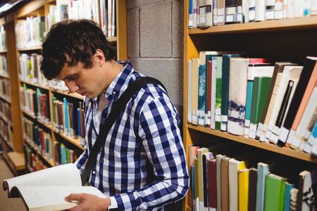 higher intelligence: Concentrated student reading book in the college library Stock Photo