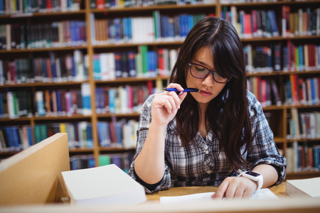 higher intelligence: Thoughtful female student looking at notes in library